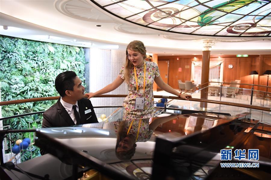 """9月26日,在""""鼓浪屿""""号国际豪华邮轮上,来自德国的游客(右)在演唱歌曲。新华社记者 林善传 摄"""