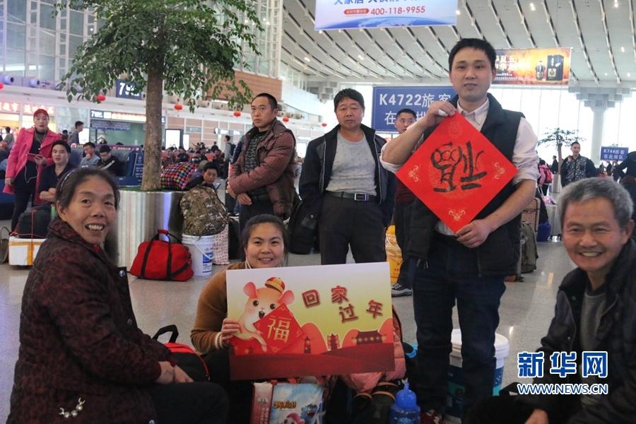 """春运首日,厦门火车站的工作人员向旅客赠送对联。这是旅客在展示领取到的""""福""""字。新华网发(万宇 摄)"""