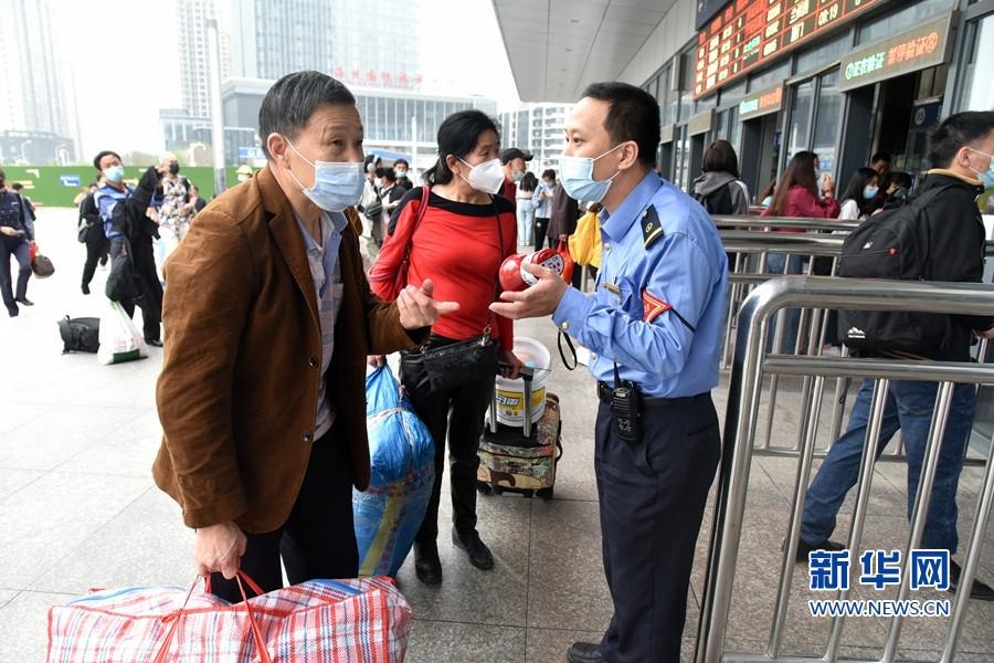 图为福州火车站工作人员回答旅客问题。新华网发(江曲 摄)