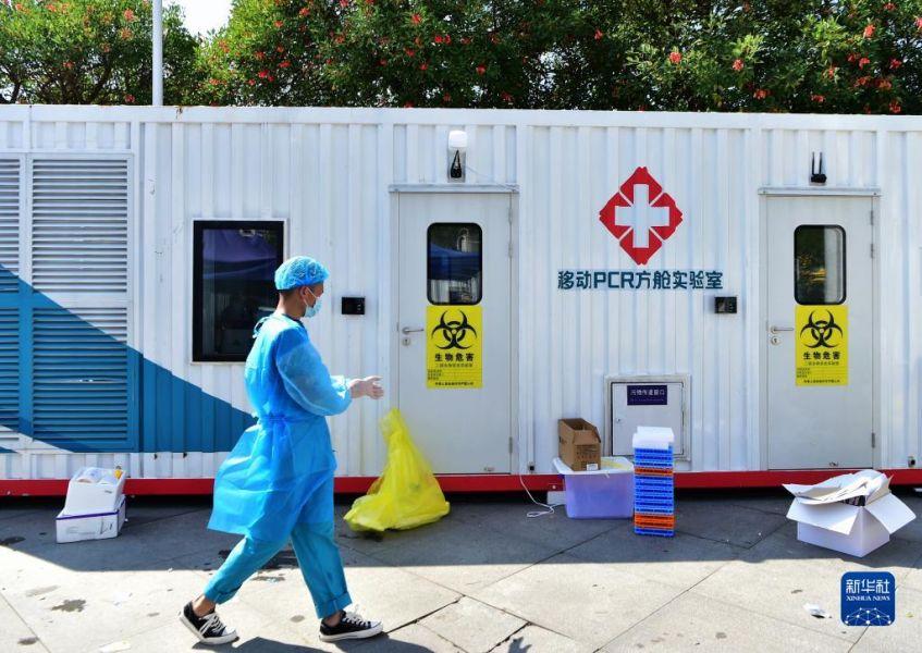 9月14日,工作人员从移动PCR方舱实验室外走过。新华社记者 魏培全 摄